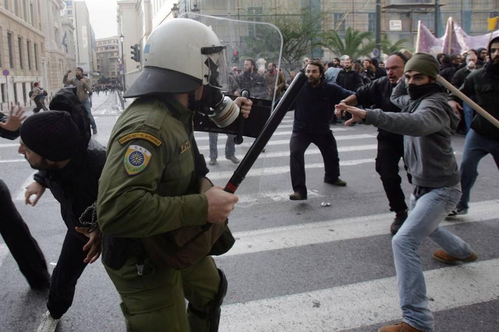 3) Полицейские и протестующие во время стычки на улице в центре греческой столицы. Демонстранты разбили витрины более чем 20 магазинов на нескольких центральных улицах Афин. (Milos Bicanski/Getty Images)