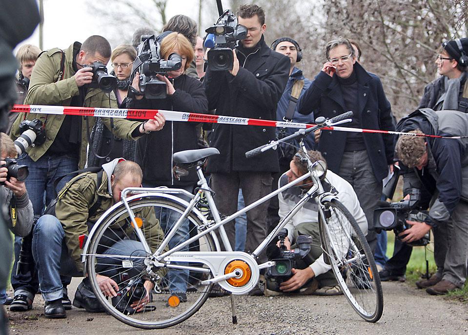 3) Журналисты пристально рассматривают велосипед на дороге в городе Шермбек, Западная Германия, после того как полиция захватила Питера Пауля Михальски, одного из двух заключенных, сбежавших из тюрьмы в Аахене, на прошлой неделе. Михальски и Майкл Хекхов, отбывающие срок за убийство и покушение на убийство, были пойманы в воскресенье. (Frank Augstein/Associated Press)