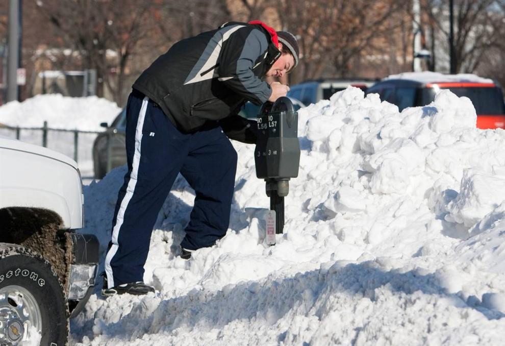 Ник Гроуб из Окланда, штат Айова, взобрался на сугроб, чтобы вставить деньги в счётчик на платной стоянке. (Nati Harnik / AP)