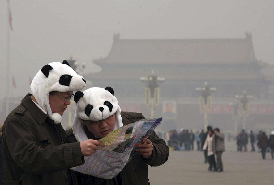 3. Два туриста в шапках в виде панды сверяются с картой на площади Тяньаньмэнь в центре Пекина. (AP Photo)