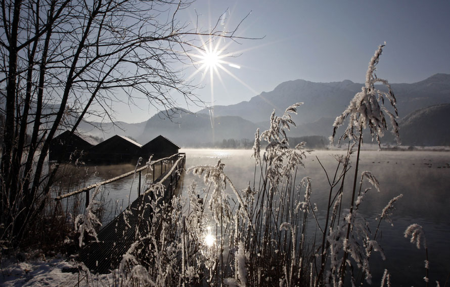 4) Солнце светит над складами лодок на Кохельском озере в Шледорф недалеко от Мурнау в южной Германии. Это озеро, площадью около шести квадратных километров, прилегает к Баварским Альпам. (AP Photo/Matthias Schrader)