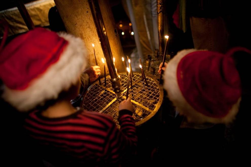 3. Дети зажигают свечи в Рождественском соборе в Вифлееме. (Uriel Sinai/Getty Images)