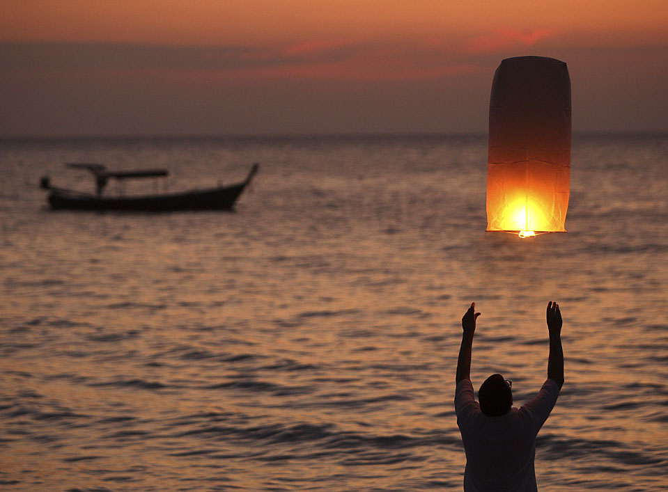 3. Турист из Финляндии выпускает воздушный фонарь в память о своем друге, погибшем пять лет назад в результате цунами в Таиланде. (Rungroj Yongrit/EPA)