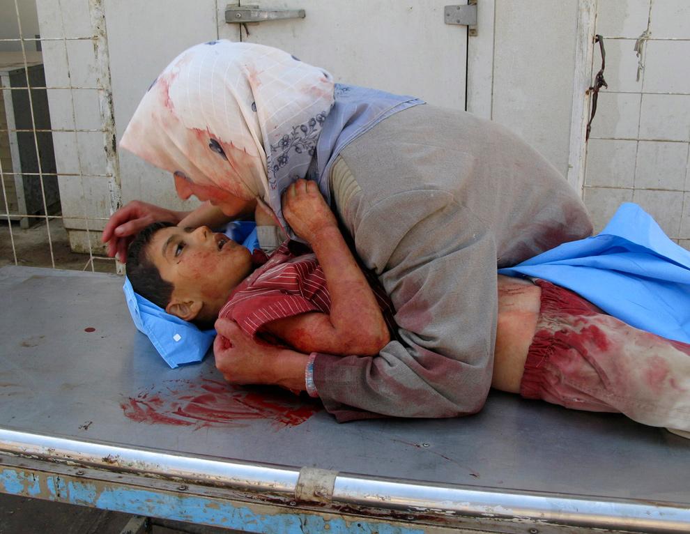 8) Женщина обнимает своего мертвого шестилетнего сына Дия Тхамера, который погиб, когда их семейный автомобиль попал под обстрел неизвестного вооруженного мужчины в столице иракской провинции Дияла Бакубе в 60 км к северо-востоку от Багдада 16 сентября 2007 года. Старший брат мальчика 10-летний Кусей был ранен. Семья возвращалась из школы, куда был записан Дия. (AP Photo/Adem Hadei)