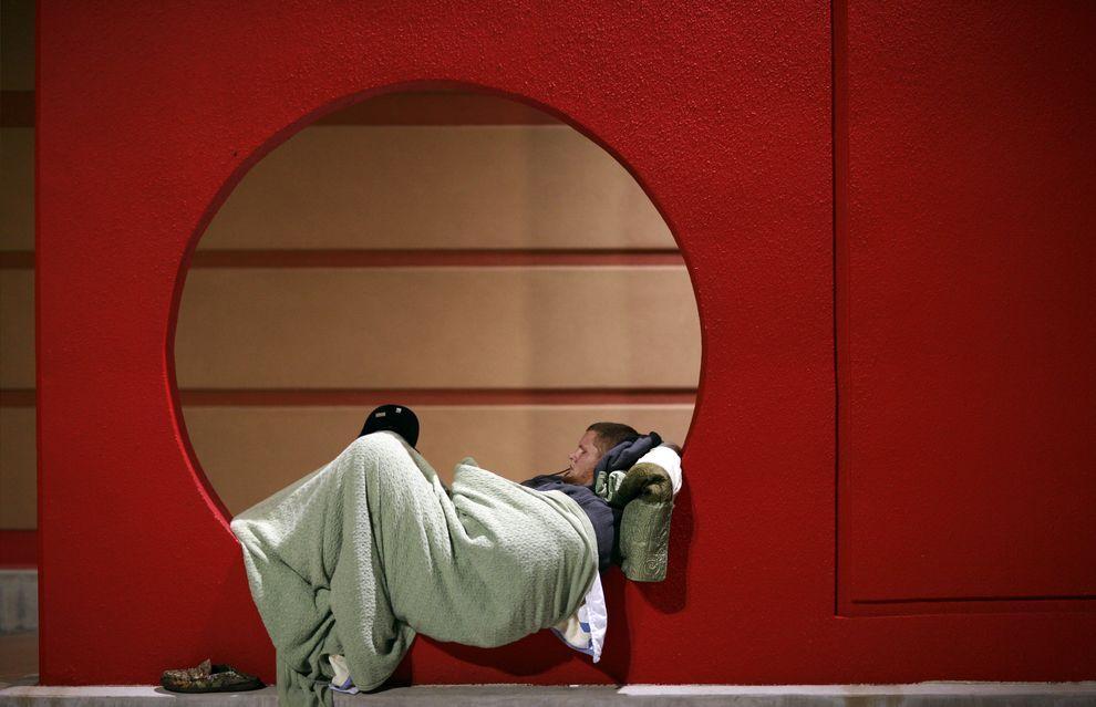 3) 5 часов утра. Покупатель, который занял очередь в магазин, прилег отдохнуть. (EPA / 27 ноября 2009/ США, Техас)