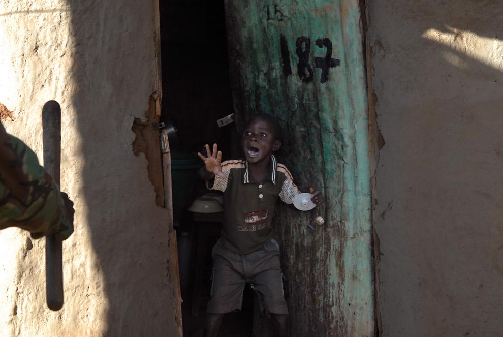 11) Кенийский мальчик кричит при виде приближающегося к его дому полицейского с дубинкой в трущобах Кибера, Найроби, 17 января 2008 года. Сотни полицейских, которые ранее столкнулись со сторонниками кенийского оппозиционного лидера Райла Одинга у входа в трущобы, начали затем обыск от дома к дому в поисках демонстрантов. (WALTER ASTRADA/AFP/Getty Images)