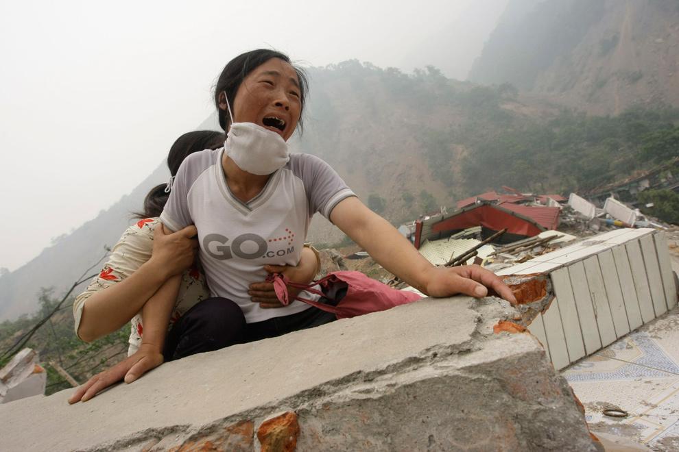 12) Женщина плачет, так как не может найти свою 4-летнюю дочь и мужа среди развалин уничтоженной землетрясением школы в округе Бэйчуань, провинция Сычуань, 17 мая 2008 года. Около 70 000 китайцев погибло в результате землетрясения и последовавших за ним оползней и наводнений. (REUTERS/Jason Lee)