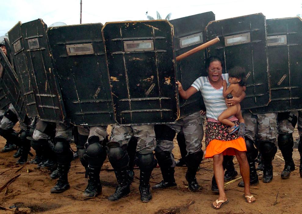 13) Местная жительница с ребенком на  руках пытается противостоять продвижению амазонской государственной полиции, которая хотела выгнать женщину и еще 200 других членов движения «Landless Movement» с частного участка земли на окраине Манауса в центре Бразильской Амазонки 11 марта 2008 года. (REUTERS/Luiz Vasconcelos-A Critica/AE)