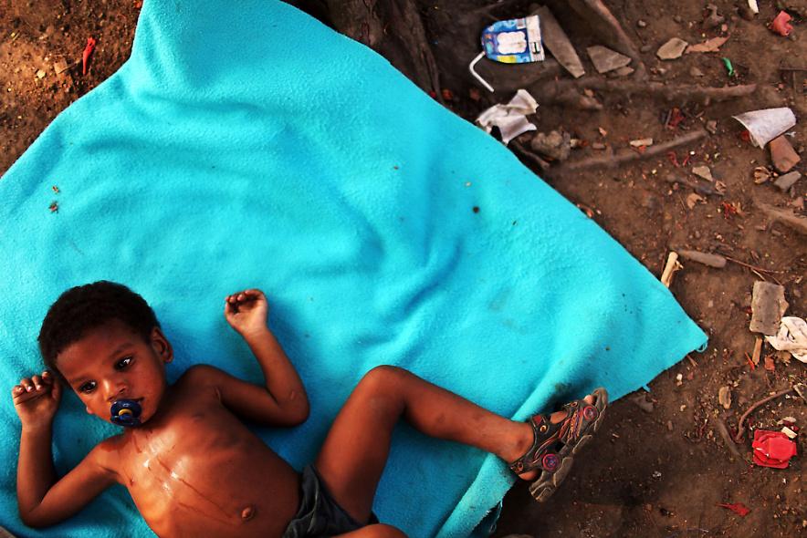 4. Ребенок на одеяле в бедном районе фавелы, или трущоб, 2 декабря 2009 года в Рио-де-Жанейро. (Photo by Spencer Platt/Getty Images)