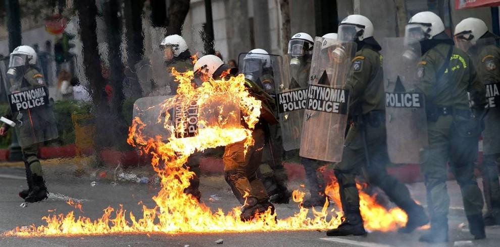 4) Одежда на одном из полицейских загорелась после того, как демонстранты забросали полицейских бутылками с зажигательной смесью на во время уличных беспорядков в Афинах. Столкновения произошли также во втором по величине греческом городе, Салониках. (Dimitri Messinis/AP)
