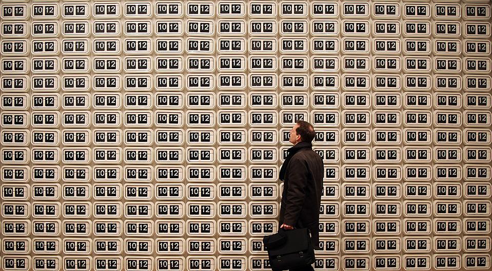"""4) Посетитель смотрит на инсталляцию Даррена Алмонда, которая носит название """"Tide 2008,"""" (Прилив 2008) и состоит из 567 цифровых настенных часов. Снимок сделан в Королевской Академии Искусств в Лондоне во вторник. На выставке которая пройдет в Королевской Академии с 3 декабря 2009 по 31 января 2010, представлены недавние работы 35 художников. (Петр MacDiarmid/Getty Images)"""