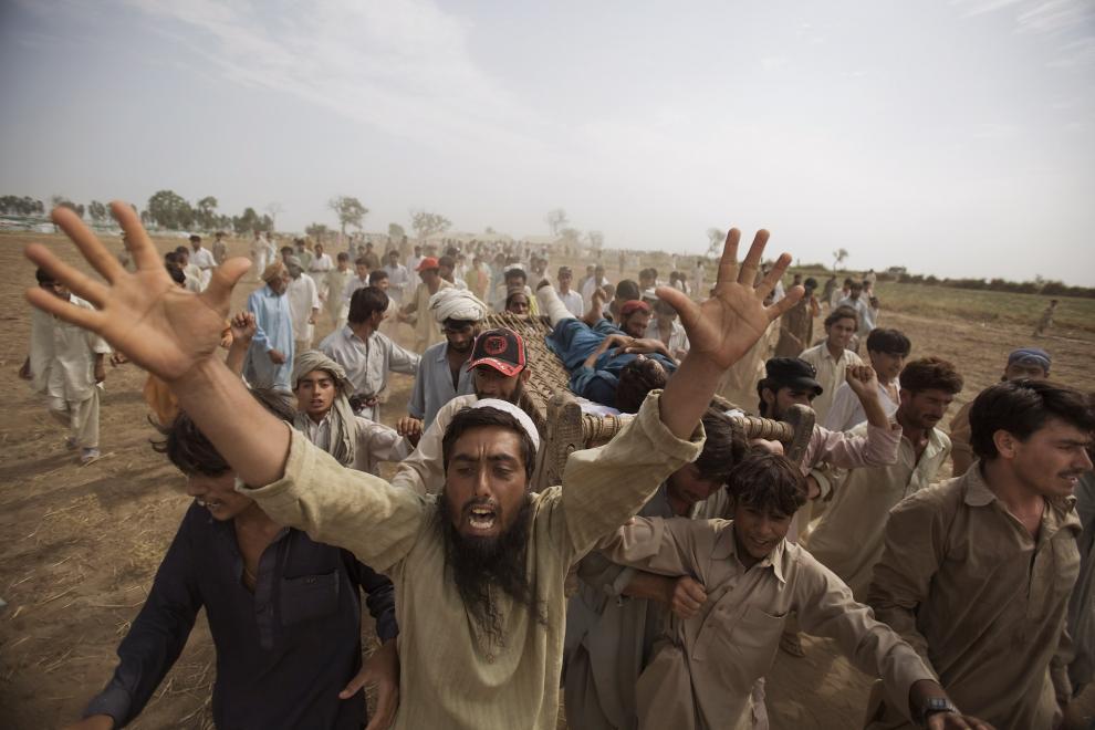 4) Толпа несет на носилках мужчину, который, по их словам, был избит полицией, когда стоял в очереди за продовольственным пайком. В результате военной операции против Талибана около 3 млн. людей стали беженцами. (Daniel Berehulak/Getty Images News/ fotobank.ua / 13 июля 2009/ Пакистан)