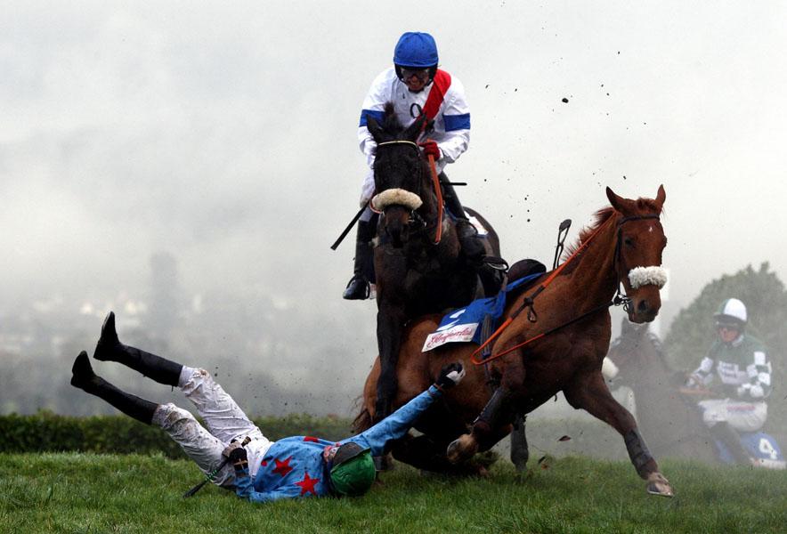 4. Алан О'Киф на коне по кличке Осоломио (сзади) пытается избежать столкновения с Кеном Вэланом на коне по кличке Звезда Ройаял Каунти, когда те упали на скачках с препятствиями на Международной встрече в Челтенхэм Рэйскорс, Англия. (AP Photo/David Davies/PA Wire)