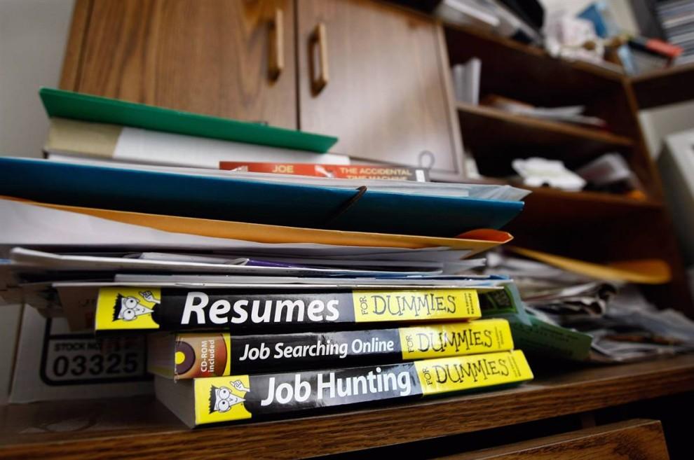 4) Литература о поиске работы («Резюме для чайников», «Поиск работы он-лайн для чайников», «Устройство на работу для чайников») лежит на столе, прежде чем все имущество Лессера вынесет из его бывшей квартиры команда по выселению. (John Moore/Getty Images)