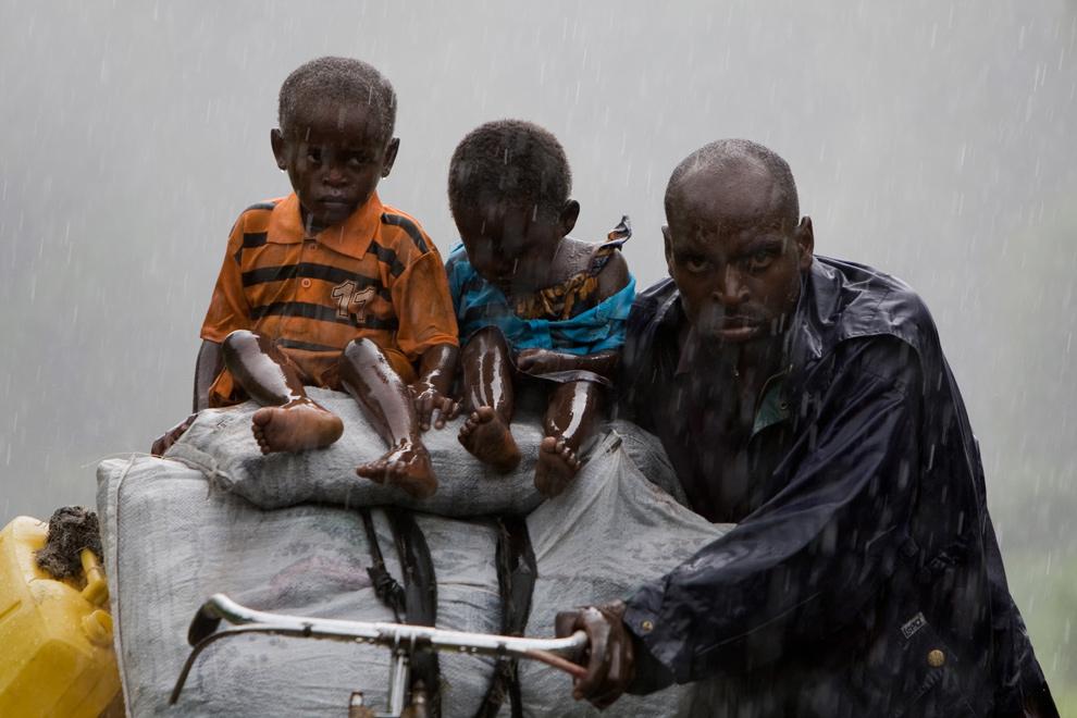 17) Внутренне перемещенные лица покидают Кибати, направляясь на север из города в поселки Кибумба и Ругари к северу от Гомы, Конго, 2 ноября 2008 года. Несколько тысяч человек были вынуждены бросить дома во время столкновения мятежников и правительственных войск на востоке Демократической Республики Конго. Теперь они начали возвращаться домой после прекращения огня. (YASUYOSHI CHIBA/AFP/Getty Images)
