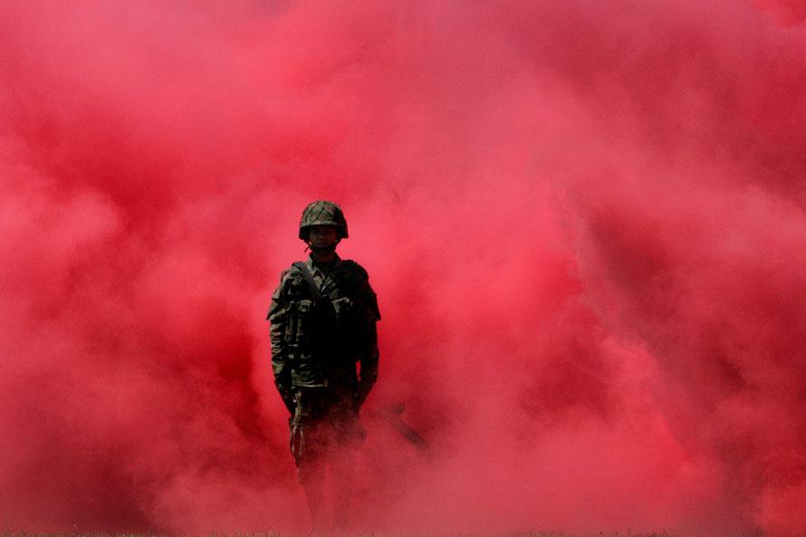 4. Солдат на военной церемонии среди дыма от сигнальных ракет в Кали, Колумбия. (AP Photo/Christian Escobar Mora)