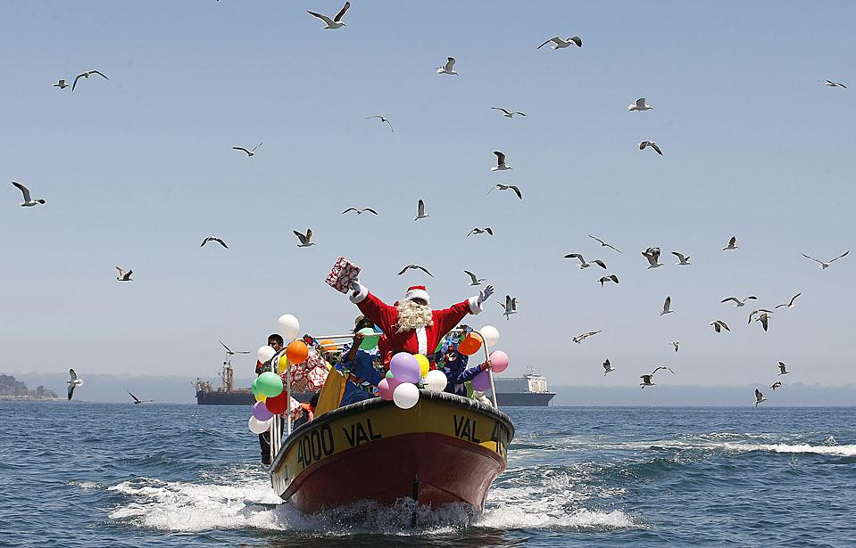 4. Рубен Торрес в костюме Санта Клауса и несколько рыбаков машут с лодки, подбадривая людей, стоящих на побережье Вальпараисо, Чили. (Eliseo Fernandez/Reuters)
