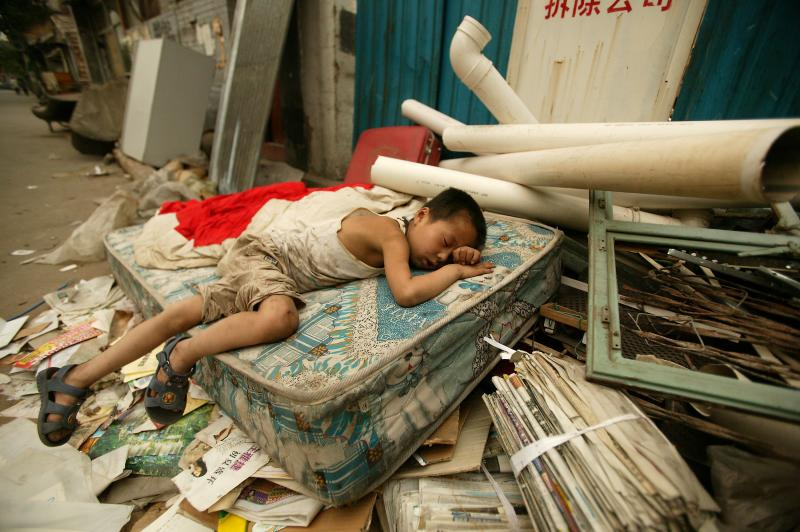 4) Китайский мальчик спит на улице на выброшенном грязном матрасе в центре Пекина 12 июня 2006 года. Борьба с бедностью остается одной из главных и самых трудных задач Китая, особенно в сельских местностях, в которых уровень бедности очень высок. (UPI Photo/Stephen Shaver)