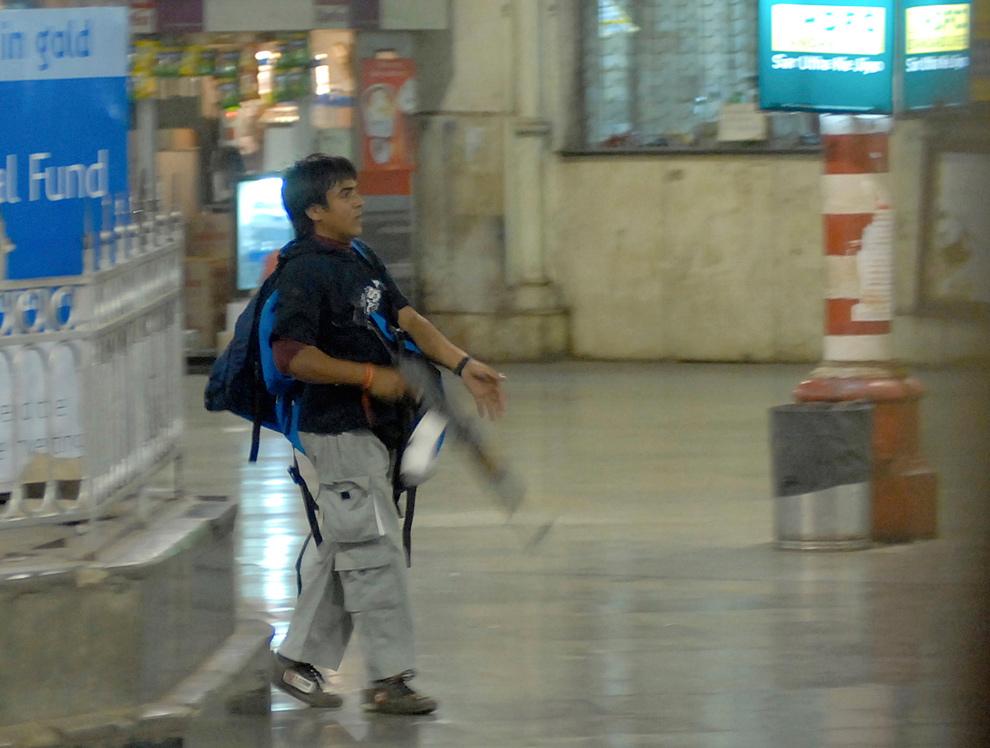 21) На этом фото, сделанном 26 ноября 2008 года, вооруженный человек, опознанный полицией, как Аджмал Касаб, идет по железнодорожной станции Чатрапати Шиваджи в Мумбаи, Индия. Касаб был единственным выжившим террористом из десяти, которые провели целую серию терактов в Мумбаи 2 ноября, убив 175 и ранив более 300 человек. (AP Photo/Mumbai Mirror, Sebastian D'souza)