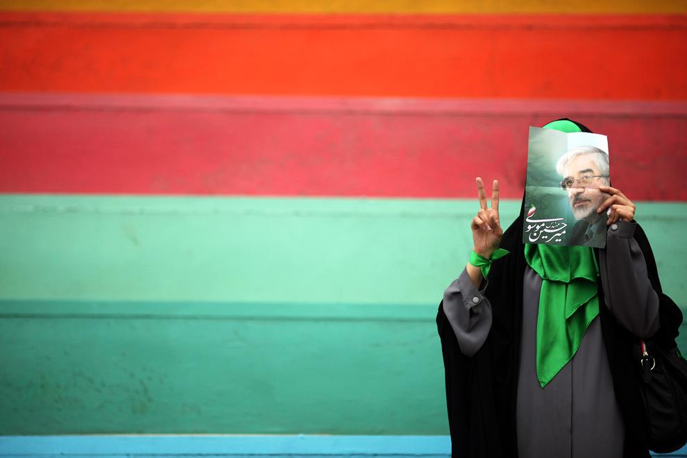 25) Иранская женщина – сторонницу бывшего премьер-министра Мир-Хосейн Мусави – закрывает лицо его фотографией во время предвыборного собрания на стадионе в Тегеране 9 июня 2009 года. (REUTERS/Damir Sagolj)