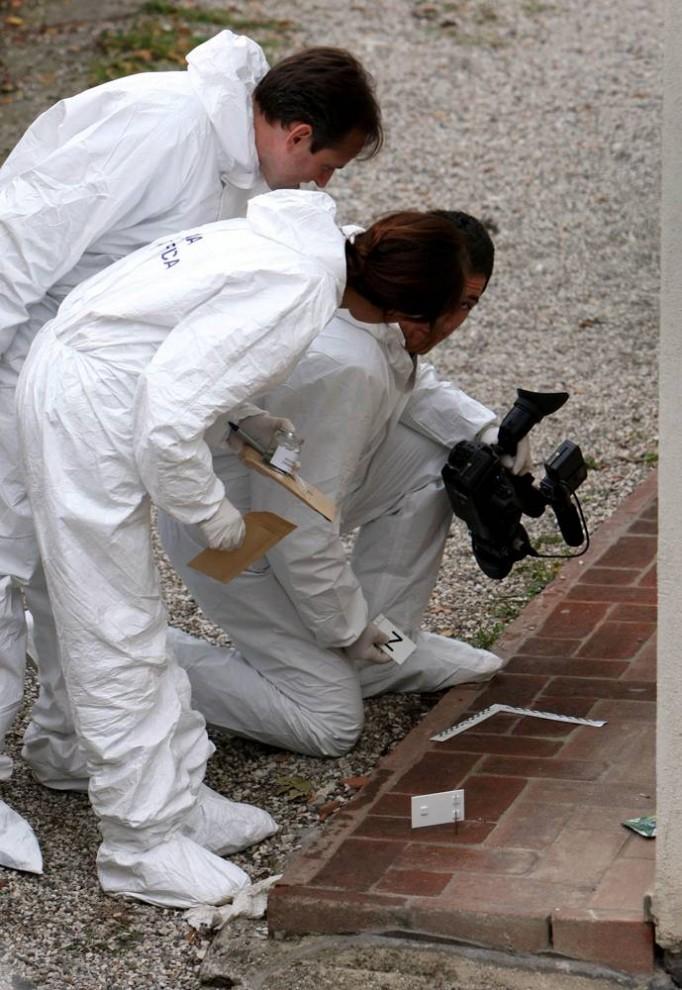 5. Судебные медэксперты исследуют итальянский дом Мередит Керчер, пока патологоанатом проводит вскрытие тела жертвы, которой перерезали горло. (Chris Radburn/AP)