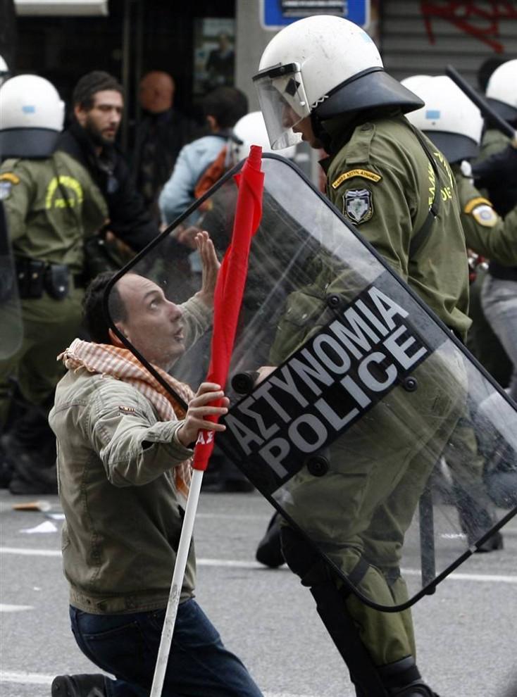 5) Протестующий стоит на коленях перед сотрудником ОМОНа в Афинах. (Kostas Tsironis/AP)