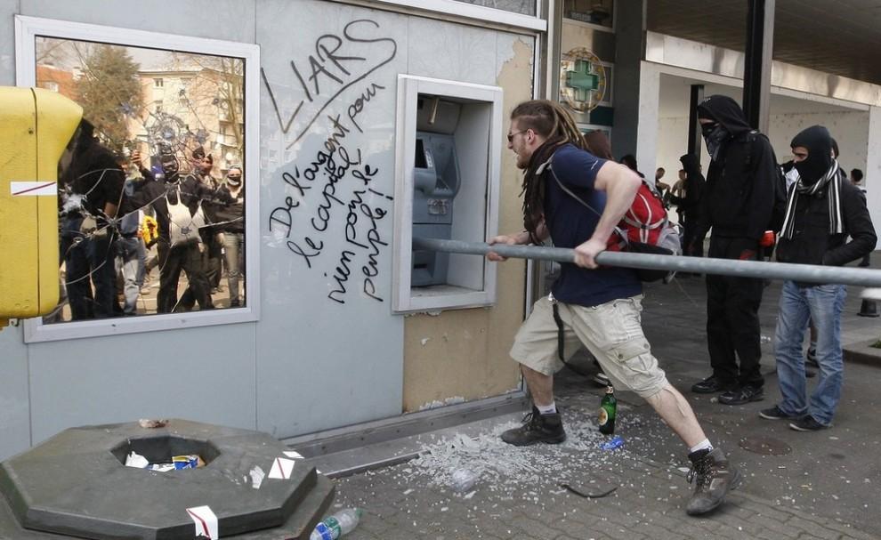 5. Демонстранты разбивают банкомат, на котором написано «Деньги для государства и ничего – для народа» во время анти-НАТОвский демонстраций в пригороде Страсбурга 4 апреля 2009 года. На той неделе Организация североатлантического договора (НАТО) праздновала свою 60-ую годовщину на саммите, проводившемся в Германии и Франции. (REUTERS/Vincent Kessler)