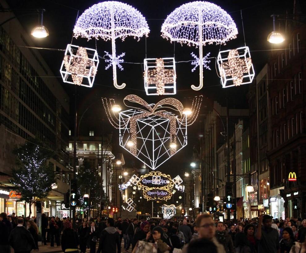 5. Прохожие идут под рождественскими гирляндами на Оксфорд Стрит вскоре после их официального включения 3 ноября в Лондоне. Две главные торговые улицы в Лондоне Вэст Энд на Оксфорд Стрит и Риджент Стрит были включены одновременно актерами Джимом Керри и Колином Фертом. (Oli Scarff / Getty Images)