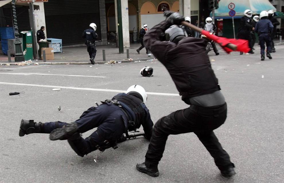 6) Участник студенческих беспорядков избивает полицейского. (Milos Bicanski/Getty Images)