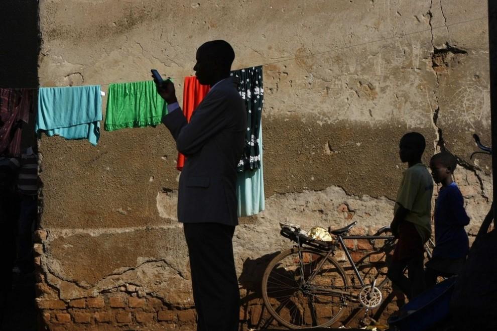 6. Представитель городской власти, сопровождающий иностранных репортеров, набирает СМС в пригороде Качуф в округе Масака южной Уганды 24 марта 2009 года. На языке луганда слово «Качуф» означает «грязь». «REUTERS/Darrin Zammit Lupi»