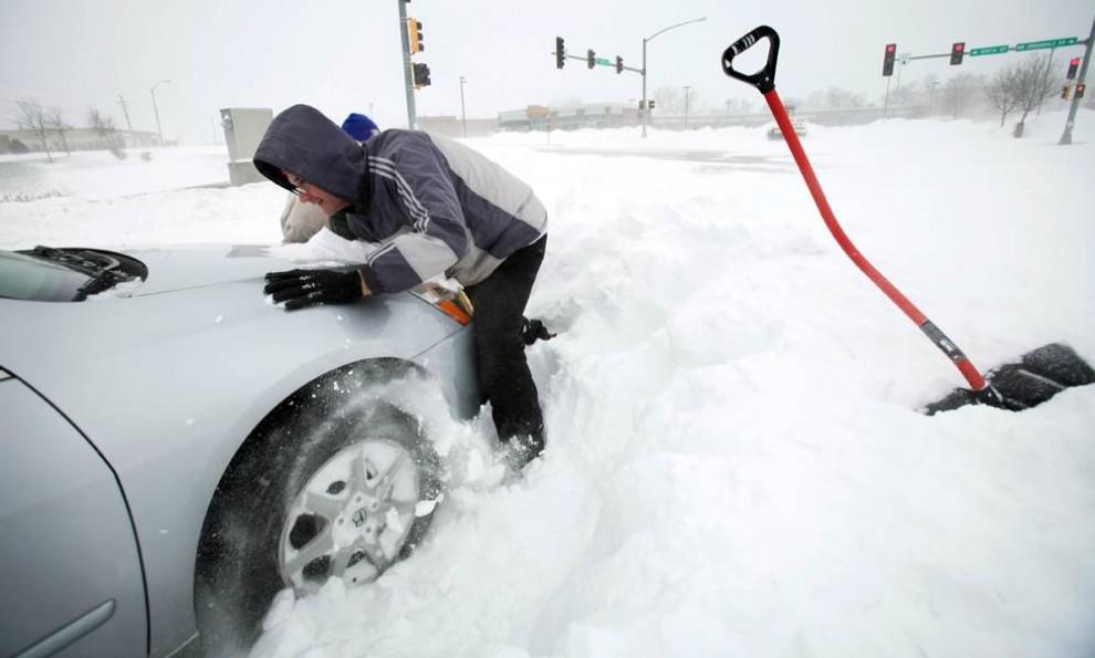 3. Проезжавший мимо водитель помогает вытолкнуть машину из снега в Де-Мойне, штат Айова, в среду. В некоторых частях штатов Иллинойс, Висконсин и Айова ожидалось более 30 см снега. Национальная метеорологическая служба обещала «чрезвычайно опасные снежные метели» и практически нулевую видимость на дорогах. Порывы ветра до 80 км в час могли создать снежные заносы от двух до четырех метров. (Charlie Neibergall / AP)