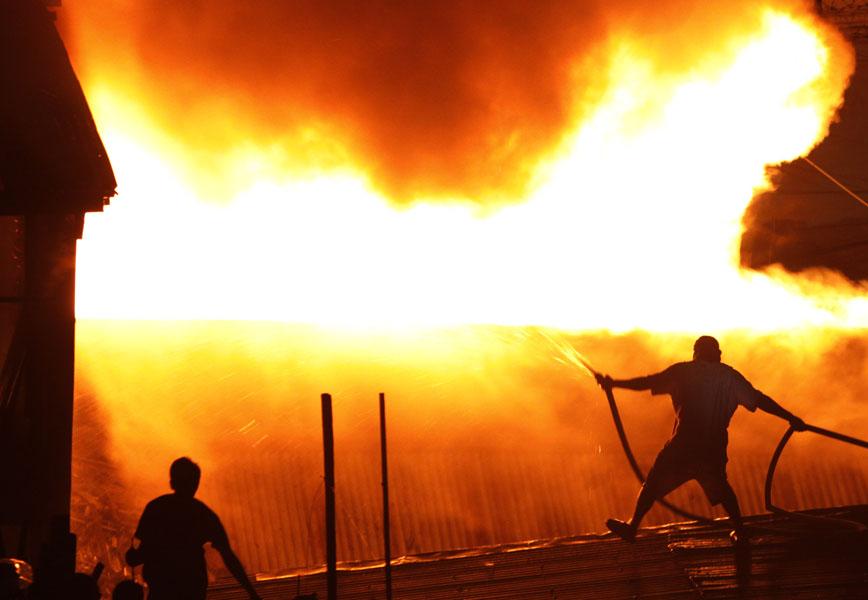 6. Жители пытаются потушить огонь, охвативший более 1000 домов в пригороде недалеко от городской тюрьмы в Маниле. Причина пожара до сих пор расследуется. (AP Photo/Aaron Favila)