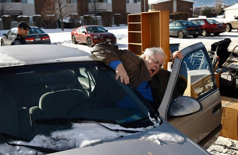 6) Лессер с трудом пытается влезть в свою машину после того, как команда по выселению вынесла его вещи из квартиры. (John Moore/Getty Images)