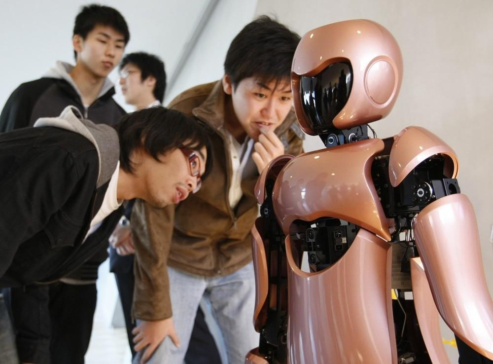 1) Студенты из Технологического института Ниппон рассматривают робота-гуманоида. (REUTERS/Toru Hanai)