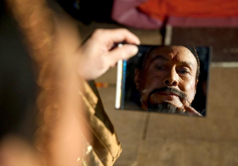 10) Цзя Чжэнь Гуд накладывает последние штрихи грима. Он - актер Китайского государственного цирка, который играет Императора в акробатической постановке Мулан. (Marco Secchi/Getty Images)