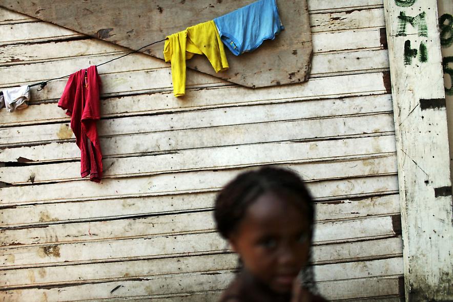 7. Девочка проходит мимо сушащейся одежды в бедном районе трущоб 2 декабря 2009 года в Рио-де-Жанейро. (Photo by Spencer Platt/Getty Images)