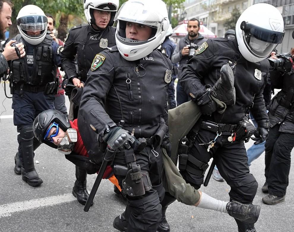 7) Полиция волочит одного из задержанных демонстрантов в центре Афин. (Louisa Gouliamaki/AFP - Getty Images)