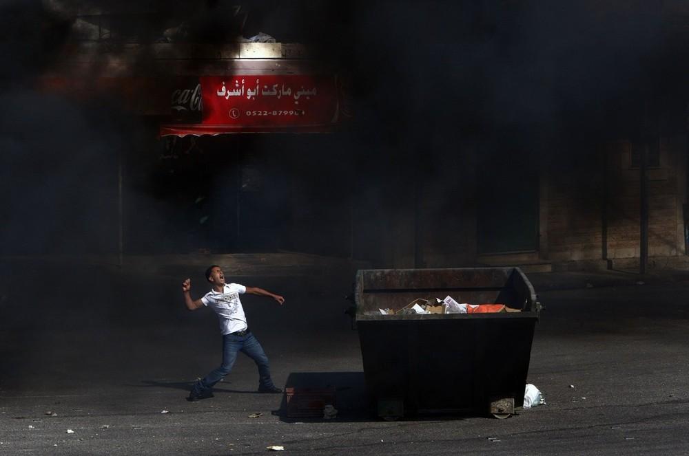 7. Палестинец бросает камень в израильских солдат на фоне дыма от сжигаемых шин во время столкновений в контрольном пункте Каландия недалеко от Западного берега реки Иордан в городе Рамаллах 9 октября 2009 года. В четверг палестинские лидеры объявили об однодневной всеобщей забастовке и предупредили о протестах по всему Иерусалиму, где столкновения в горячих точках у мечети ал-Акса две недели назад дали начало протестам в городе. Израиль преуменьшает значение палестинских предупреждений о том, что их тактика безопасности вышла на новый уровень. (REUTERS/Yannis Behrakis)