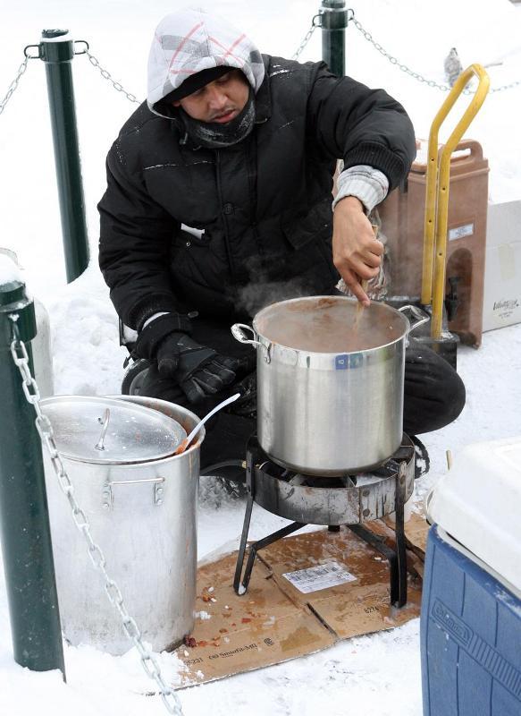 7. Джей Синг мешает чили, пока Арт Повлоески и другие добровольцы из Уличной Церкви раздают горячую еду бездомным перед мэрией Калгари в 29-градусный мороз 13 декабря 2009 года.