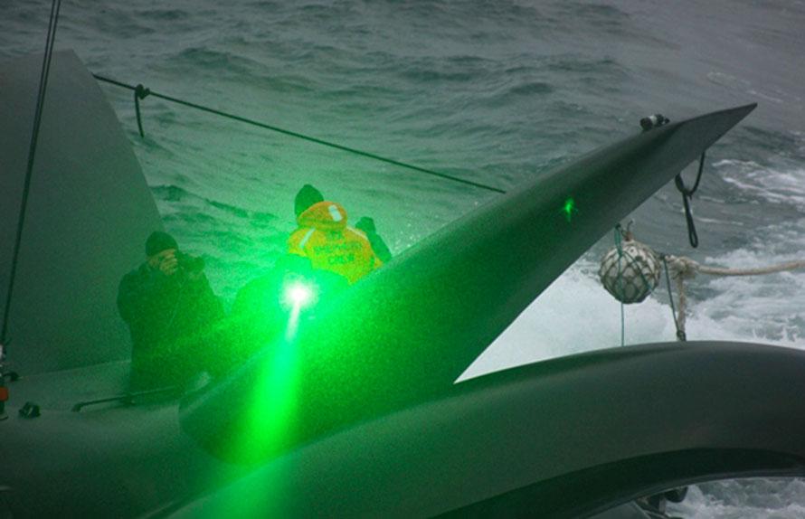 7. Активист сообщества по сохранению морских видов сигналит зеленым лазером с палубы нового судна команды под названием «Ady Gil» японскому китобойному судну «Shonan Maru No. 2» во время их встречи в открытом море утром в среду. «Ady Gil» - высокоскоростной тримаран, ранее известный как «Earthrace», который недавно установил мировой рекорд по кругосветному плаванию. (AP Photo/Institute of Cetacean Research)