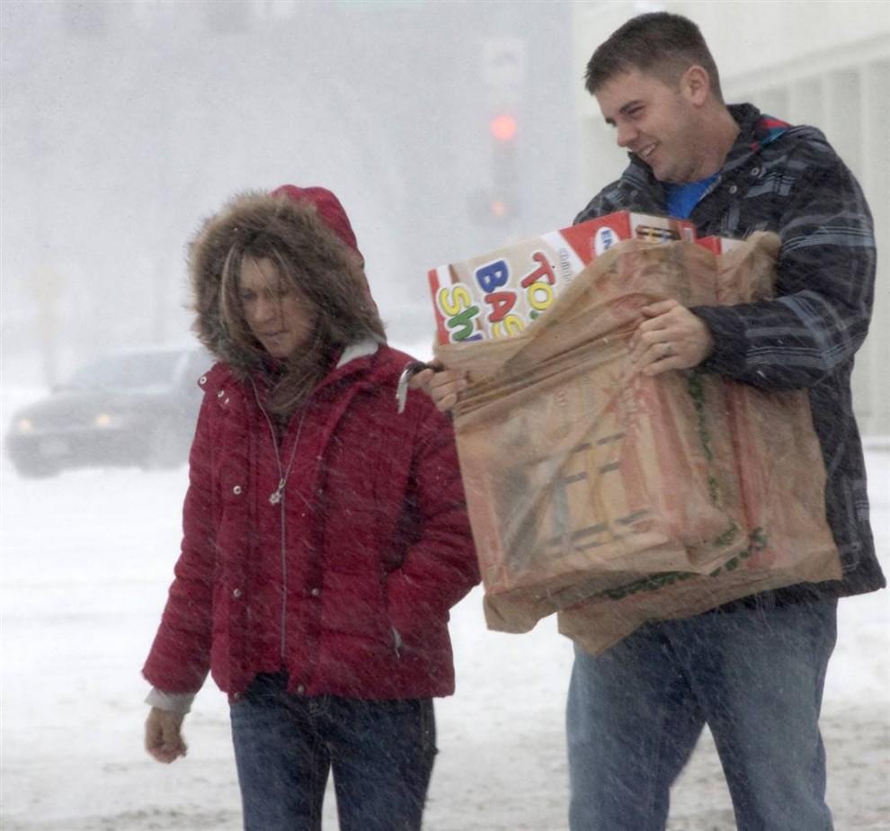7. Любители покупок делают покупки и в последний момент, несмотря на погоду, накануне Рождества в Омахе, штат Небраска. (Nati Harnik/AP)