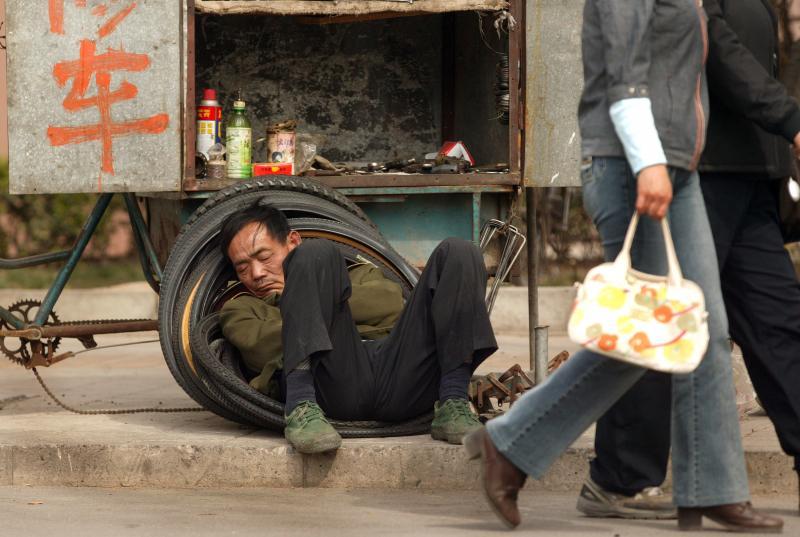7) Китайский специалист по ремонту велосипедов отдыхает на покрышках рядом со своей мастерской в центре Пекина 8 апреля 2007 года. В городе доходы выросли в 3,2 раза по сравнению с доходами в сельских районах (жители которых зарабатывали всего 413 долларов в год на 2005 год), поднявшись с отметки 2,5 в 1978 году, когда Китай начал свою реформу экономики. (UPI Photo/Stephen Shaver)