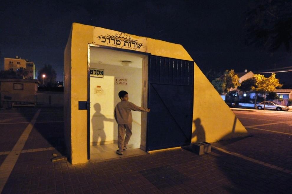 8. Израильский мальчик идет в бомбоубежище в южном городе Ашкелон 4 января 2009 года. Израильские войска и танки разделили Сектор Газа и окружили его главный город в воскресенье в ответ на атаку группировки «Хамас», которая убила 500 палестинцев, включая большое число гражданских. «Хамас» напала на южный Израиль, несмотря на все усилия самой мощной армии Ближнего Востока достичь цели израильских лидеров в том, чтобы избавиться от угрозы пограничных перестрелок. (REUTERS/Amir Cohen)