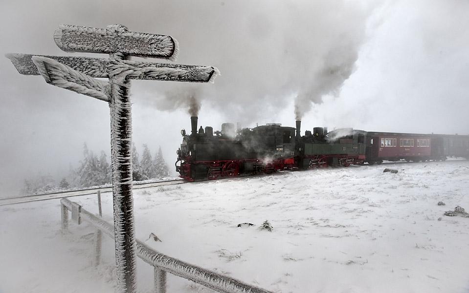 8) Состав, который везет паровоз Brockenbahn, прибывает на горную станцию, в Восточной Германии. Во времена Холодной Войны, Brockenbahn использовался для поставок в гарнизон, расположенный на горной вершине, и доступ гражданских сюда был ограничен.  Эта линия была вновь открыта для публики в 1991 году, и каждый год паровозы привлекают тысяч туристов. (Eckehard Schulaz/Associated Press)