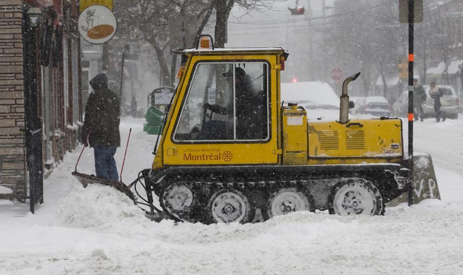 8. Городской рабочий расчищает проезд на перекрестке улиц Jeanne Mance St. и Saint-Viateur St. в Монреале 9 декабря 2009 года. Это был первый ильный снегопад зимнего сезона 2009-10.