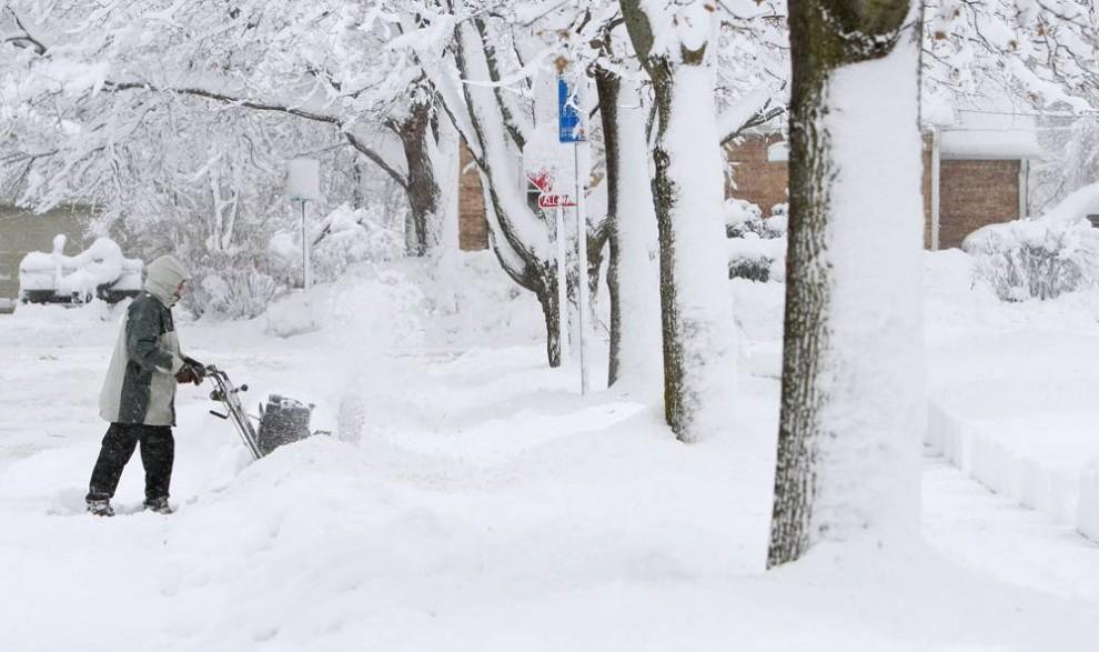 5. Том Бланкенхайм убирает снег с проезда к своему дому и к дому соседа в Мэдисоне, штат Висконсин. Мэдисон и соседние окрестности завалило от 38 до 45 см снега, и метеорологи сообщают, что это не предел. (Andy Manis / Getty Images)