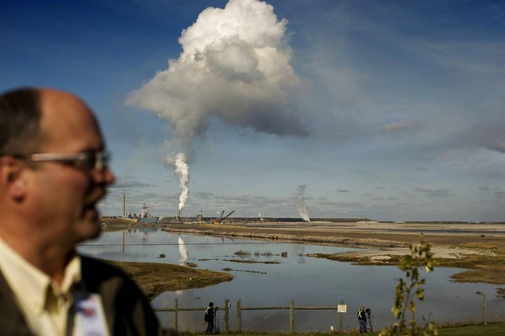 8. На заднем плане вы видите «Syncrude» - перерабатывающий завод крупнейшего производителя нефтеносного песка в Канаде. Эксперт экологической службы Стив Годет говорит, что компания решила восстановить здешние территории практически до их первоначального вида, как только добыча нефти завершится. Некоторые территории уже были восстановлены, там уже пасется около 300 бизонов. Также на фото виден пруд-накопитель отходов – побочный продукт процесса разработки месторождений. В пруду содержится глина, вода, песок, углеводород и тяжелые металлы, оставшиеся после того, как вода вымыла из песка нефть в процессе отщепления. Подобные накопители отходов довольно токсичны, в 2008 году здесь погибло около 1500 уток. Генераторы шума, созданные специально, чтобы отпугивать птиц, не помогли. «Syncrude» могут предъявить обвинения. (Jon Lowenstein/Consequences by NOOR)