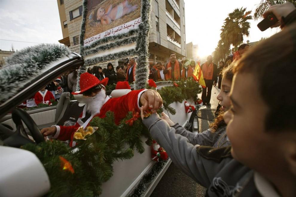 8. Мужчина в костюме Санта Клауса раздает подарки израильским детям на ежегодной рождественской процессии в северном городе Назарет . (Gil Cohen Magen/Reuters)