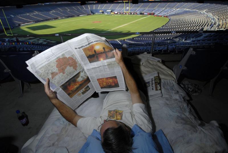 8) Ричард Доринг, эвакуированный из собственного дома из-за лесных пожаров, читает газету на матрасе 24 октября 2007 года на стадионе Квальком в Сан-Диего. Около миллиона человек были вынуждены перейти во временные убежища из-за лесных пожаров, которые сожгли 109 265 гектаров лесов и более 1250 домов. (UPI Photo / Earl S. Cryer)
