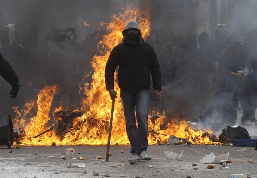 9) Анархист на фоне горящего мусора в ходе уличных беспорядков в Афинах. (Petros Giannakouris/AP)